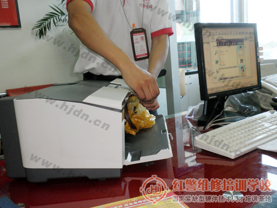 红警打印机维修工程师陈师傅正在对EPSON C1100喷墨打印机进行初步检测
